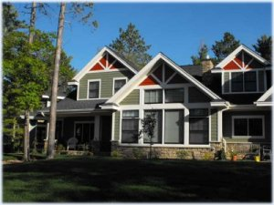 Painting exterior siding and detailed trim on a northern Minnesota home